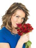 Молодая привлекательная женщина держа пук красных роз стоковые фото
