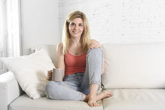 Молодая привлекательная женщина держа чашку кофе сидя на усмехаться кресла софы дома счастливый Стоковое Фото
