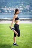 Молодая привлекательная женщина делая тренировки outdoors Стоковые Изображения