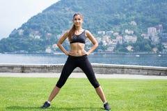 Молодая привлекательная женщина делая тренировки outdoors Стоковое Изображение