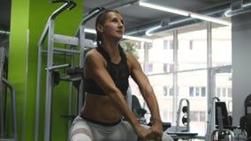 Молодая привлекательная женщина делая тренировку kettlebell во время разминки crossfit на спортзале Девушка с тренировкой тела фи акции видеоматериалы