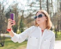 Молодая привлекательная женщина делая фото selfie на smartphone Стоковое Изображение RF