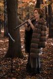 Молодая привлекательная женщина играя oboe против музыкальной стойки Стоковые Фотографии RF