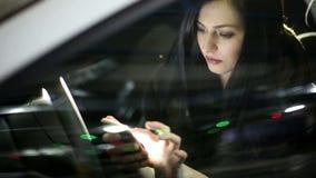 Молодая привлекательная женщина используя мобильный телефон в автомобиле на подземной автостоянке