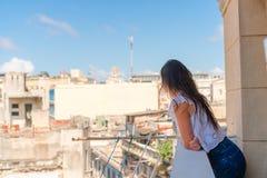 Молодая привлекательная женщина на старом балконе в квартире в Гаване с соперничает старых городка и домов Стоковое Фото