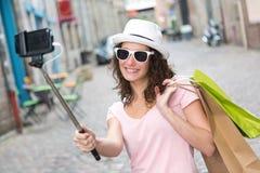 Молодая привлекательная женщина принимая selfie пока ходящ по магазинам Стоковое Фото