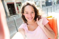 Молодая привлекательная женщина принимая selfie пока ходящ по магазинам Стоковое Изображение RF