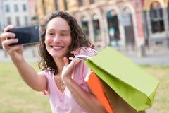 Молодая привлекательная женщина принимая selfie пока ходящ по магазинам Стоковая Фотография RF