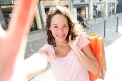 Молодая привлекательная женщина принимая selfie пока ходящ по магазинам Стоковые Фотографии RF
