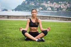 Молодая привлекательная женщина размышляя на траве outdoors Стоковое Изображение RF