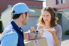 Молодая привлекательная женщина сердитая против работника доставляющего покупки на дом Стоковые Фото