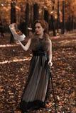 Молодая привлекательная женщина стоя в парке падения и держа горя музыкальные примечания в руке, полагаясь на тросточке Стоковая Фотография