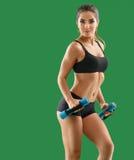 Молодая привлекательная женщина с гантелями в ее руках представляя в stu стоковое изображение