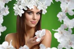 Молодая привлекательная женщина с цветками в ее волосах представляя в студии стоковое изображение