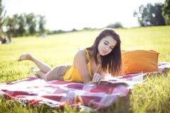 Молодая привлекательная женщина читая кассету Стоковое Изображение