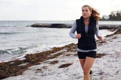 Молодая привлекательная женщина jogging на песчаном пляже стоковые фотографии rf