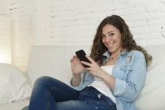 Молодая привлекательная испанская женщина используя мобильный телефон app или отправляющ СМС на домашнем кресле Стоковая Фотография RF