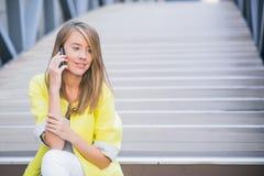 Молодая привлекательная коммерсантка сидя на лестницах и используя умный телефон Стоковая Фотография RF