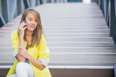 Молодая привлекательная коммерсантка сидя на мосте и используя умный телефон Стоковое фото RF