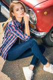 Молодая привлекательная модель сидит около ретро автомобиля Стоковая Фотография