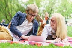 Молодая привлекательная пара нося стекла работающ или изучающ при примечание и ручка книги компьтер-книжки лежа на одеяле в зелен Стоковое Изображение RF