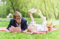 Молодая привлекательная пара нося стекла работающ или изучающ при примечание и ручка книги компьтер-книжки лежа на одеяле в зелен Стоковые Изображения RF
