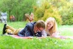 Молодая привлекательная пара нося стекла работающ или изучающ при примечание и ручка книги компьтер-книжки лежа на одеяле в зелен Стоковое Изображение