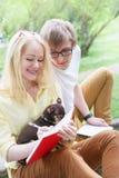 Молодая привлекательная пара нося стекла работающ или изучающ при примечание и ручка книги компьтер-книжки сидя на одеяле в зелен Стоковое фото RF