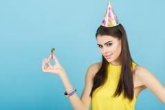 Молодая привлекательная усмехаясь женщина с шляпой и свистком дня рождения на голубой предпосылке Торжество и партия Стоковые Фото