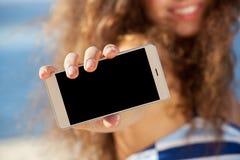 Молодая, привлекательная, усмехаясь молодая женщина на пляже держа мобильный телефон Стоковая Фотография RF