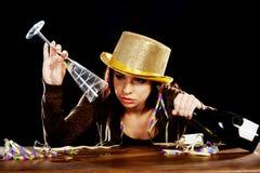 Молодая пьяная женщина сидя столом. Стоковые Фото