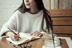Молодая работа девушки битника в кафе, с блокнотом в кафе около времени обеда окна с кофе стоковые изображения