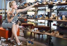 Молодая радостная девушка пробуя на выбранных ботинках Стоковые Фотографии RF