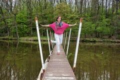 Молодая радостная женщина представляет на мосте с behin леса Стоковое Изображение RF