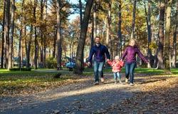 Молодая радостная кавказская семья в парке стоковое фото