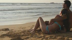 Молодая романтичная пара наслаждается красивым видом сидя на пляже и обнимать Женщина и человек сидят совместно внутри Стоковое Фото