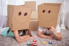 Молодая дружелюбная семья делает потеху с упаковкой стоковое изображение rf