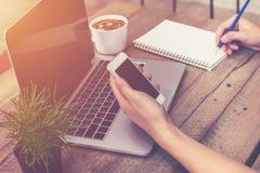 Молодая рука бизнесмена держа телефон и используя портативный компьютер Стоковые Фотографии RF