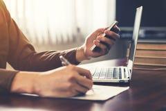 Молодая рука бизнесмена используя телефон и писчую бумагу в  Стоковое Фото