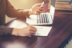 Молодая рука бизнесмена используя телефон и писчую бумагу в  Стоковая Фотография