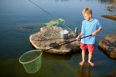 Молодая рыбная ловля мальчика на озере лет Стоковая Фотография