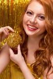 Молодая рыжеволосая девушка на предпосылке золота стоковое фото rf