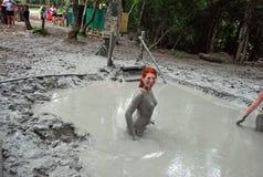 Молодая рыжеволосая девушка принимает ванну грязи в горах стоковая фотография rf