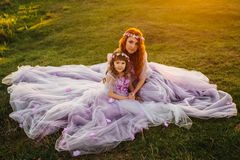 Молодая рыжеволосая мать при ее дочь отдыхая на природе в солнце Стоковое Фото