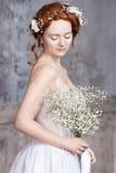 Молодая рыжеволосая невеста в элегантном белом платье свадьбы Она стоит, она глаза мечтательные закрытые, Стоковое фото RF