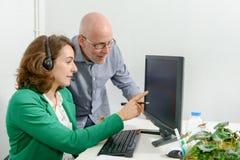 Молодая секретарша и его босс в офисе Стоковые Фотографии RF