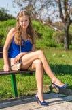Молодая сексуальная дама в голубом платье сидя на скамейке в парке Стоковая Фотография