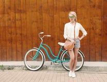 Молодая сексуальная белокурая девушка стоит около винтажного зеленого велосипеда с коричневой винтажной сумкой в зеленых солнечны Стоковые Фотографии RF
