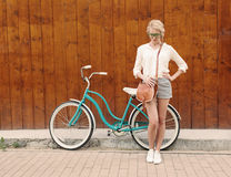 Молодая сексуальная белокурая девушка стоит около винтажного зеленого велосипеда с коричневой винтажной сумкой в зеленых солнечны Стоковая Фотография