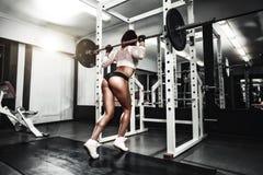 Молодая сексуальная девушка брюнет в спортзале делая сидение на корточках с штангой Стоковые Фотографии RF